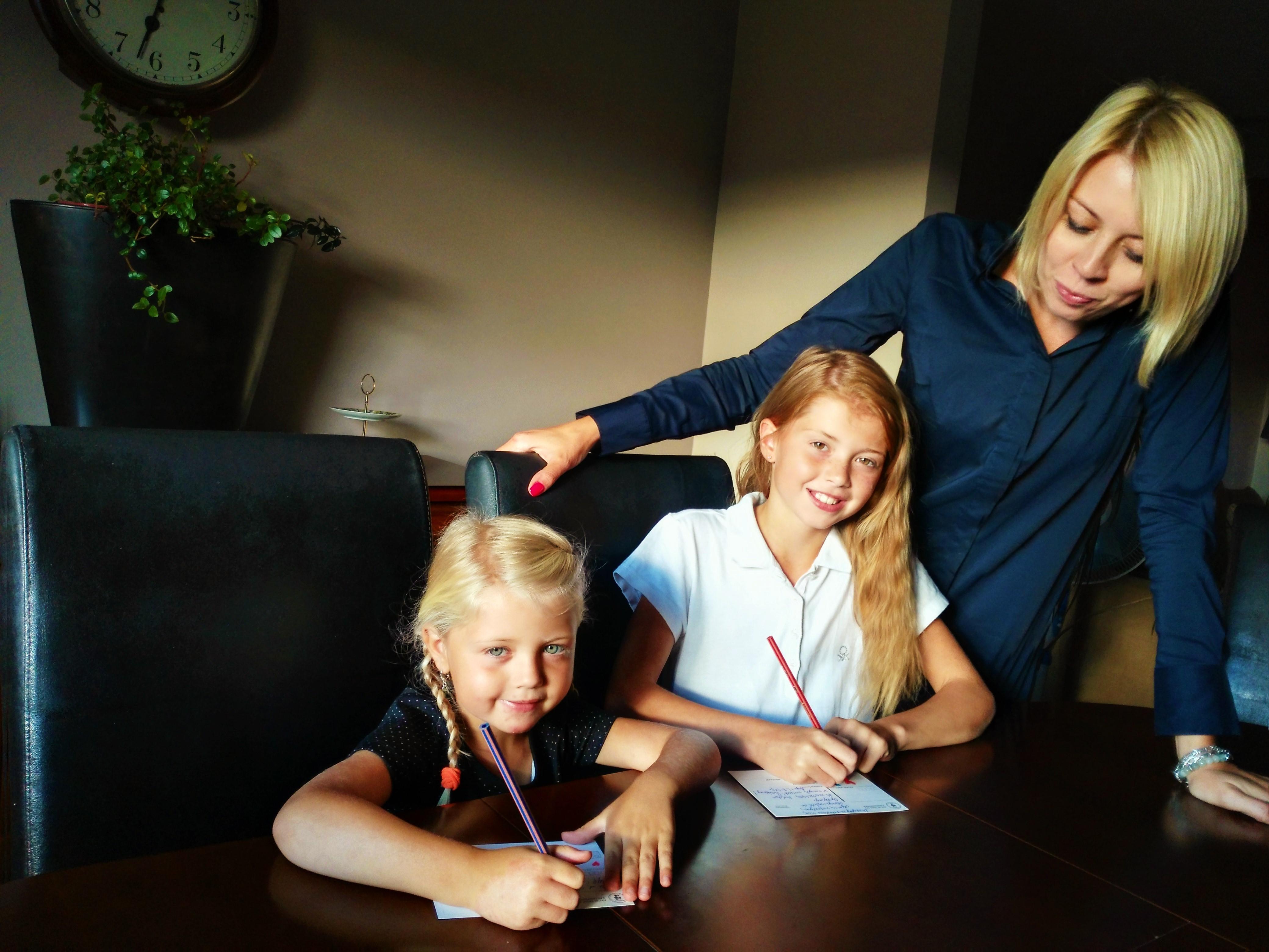 BohaterON - dziewczynki wypełniają kartki życzeniami do Powstańców